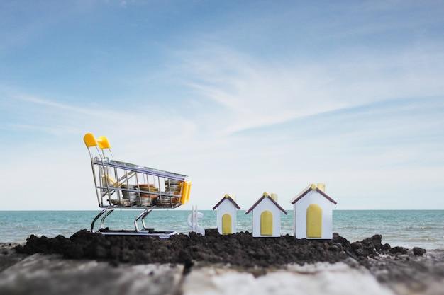 Casa di modello e moneta nel concetto del carrello per il risparmio di ipoteca