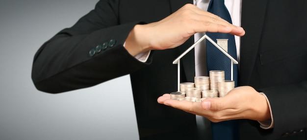 Casa di monete in crescita sulla pila di monete in mano. concetto di investimento