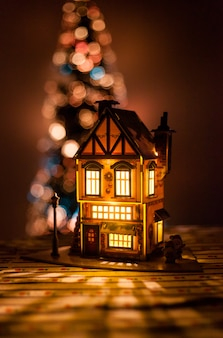 Casa di natale fatta con le tue mani di cartone e carta, una casa con una lampadina e un albero di natale