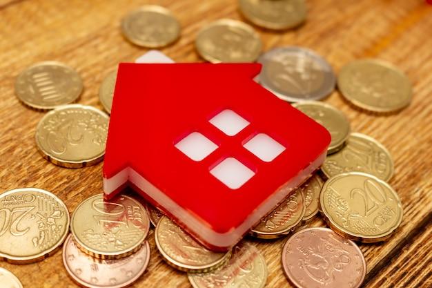Casa domestica rossa sulla fine d'acquisto dello spazio della copia del modello della spesa di concetto del bene immobile del pacchetto del mucchio del dollaro del fondo delle monete sul fuoco selettivo del fondo