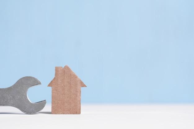 Casa e chiave del ritaglio del cartone sull'azzurro con copyspace.