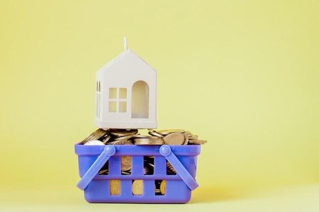 Casa e moneta di modello nel concetto del cestino della spesa per il risparmio di ipoteca sul fondo giallo