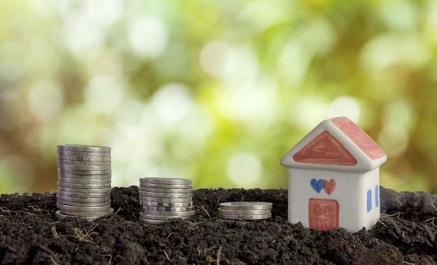 Casa e monete nel terreno, risparmiando denaro per costruire un concetto di casa