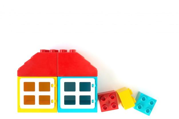 Casa fatta di piccoli e grandi mattoni di plastica costruttore su bianco