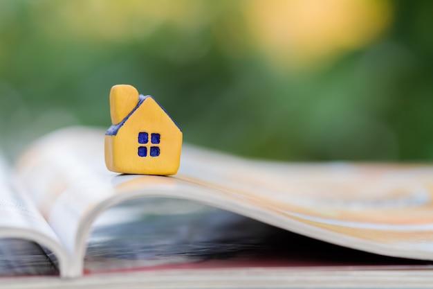 Casa giocattolo giallo in miniatura su una rivista aperta
