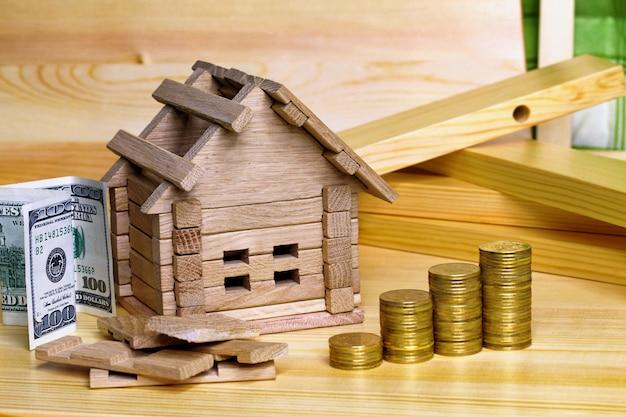 Casa in legno con monete. (concetto di finanza, proprietà e mutuo per la casa). miniatura della casa con una pila di monete. denaro per l'edificio e dettagli del nuovo edificio. acquisto di una nuova casa.