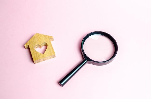 Casa in legno con un cuore e una lente di ingrandimento