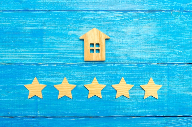 Casa in legno e cinque stelle su uno sfondo grigio. valutazione delle case e proprietà privata.