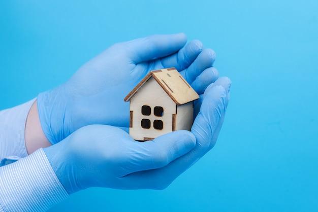 Casa in legno nelle mani di guanti medicali. concetto di protezione e assistenza