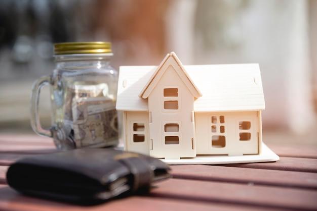 Casa in miniatura con barattolo di risparmio e portafoglio
