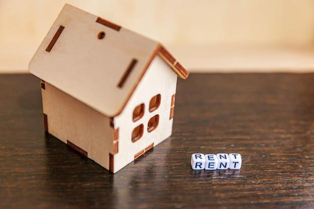 Casa in miniatura del modello del giocattolo con la parola affitta delle lettere di affitto sul contesto di legno