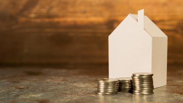 Casa in miniatura di carta con una pila di monete sul pavimento contro il contesto in legno