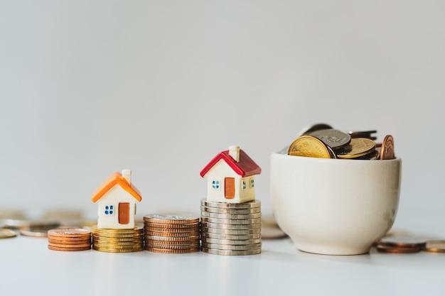 Casa miniatura sul mucchio delle monete con le monete piene in tazza facendo uso di bene immobile della proprietà di affari e concetto finanziario