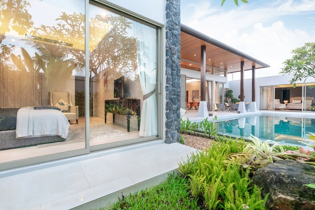 Casa o casa design esterno che mostra villa con piscina tropicale con giardino e camera da letto