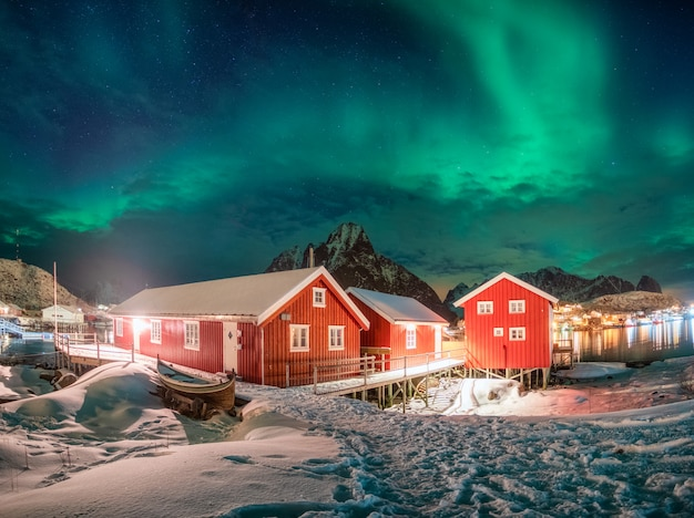Casa rossa nel villaggio di pescatori con aurora boreale sopra l'oceano artico in inverno durante la notte