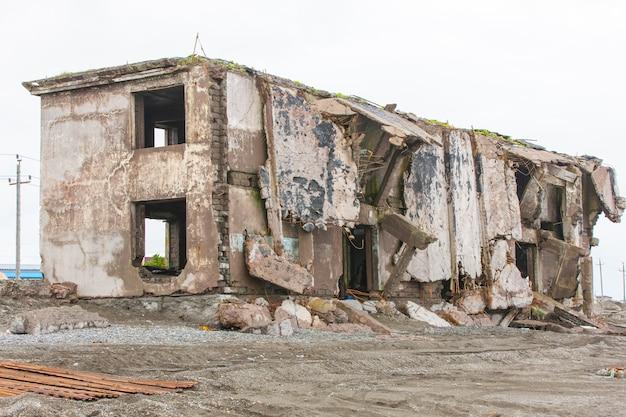 Casa rovinata sulla sabbia vicino al mare.