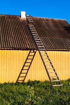 Casa rurale gialla sveglia con le scale di legno in campagna.