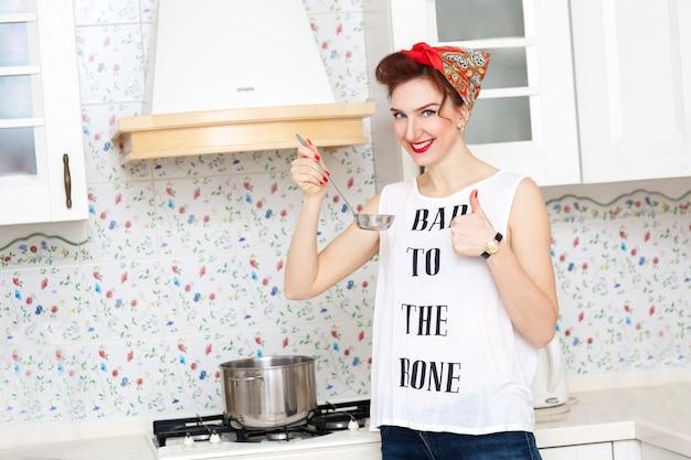 Casalinga allegra in un fazzoletto rosso in cucina