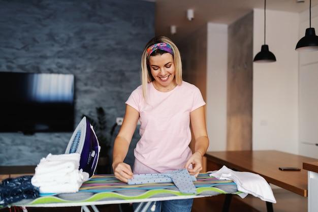 Casalinga bionda sorridente attraente in piedi in soggiorno e stirare i vestiti.