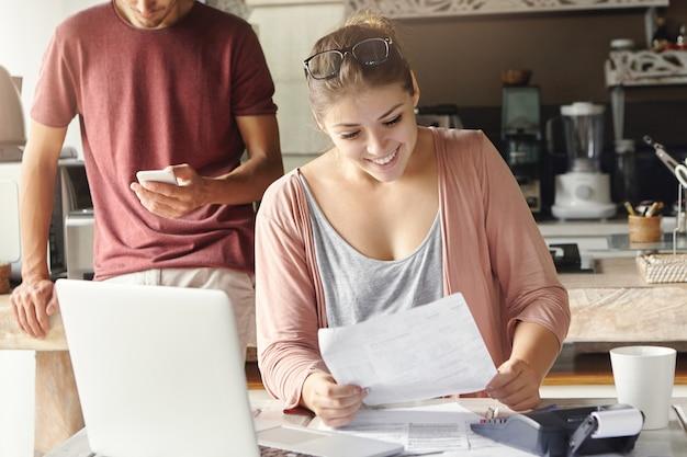 Casalinga caucasica attraente che tiene pezzo di carta, leggendo la lettera dalla banca