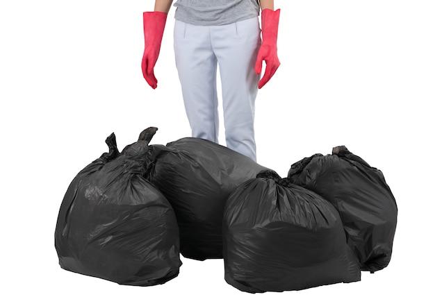 Casalinga che sta fra le borse di immondizia isolate su bianco