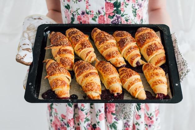Casalinga che tiene i croissant pronti di una teglia