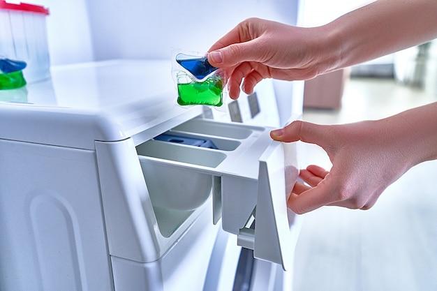 Casalinga che usando la capsula della polvere della lavanderia per lavare i vestiti variopinti