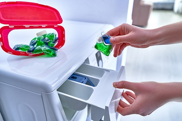 Casalinga che utilizza la capsula di gel per bucato per lavare i panni