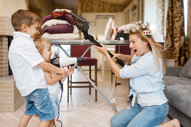 Casalinga con bambini che giocano a aspirapolvere e asciugacapelli all'asse da stiro. donna con bambino a fare i lavori domestici a casa insieme. persona di sesso femminile con la figlia che si diverte nella loro casa