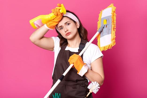 Casalinga esausta ritratto stanca delle faccende domestiche, indossa maglietta bianca, grembiule marrone, fascia per capelli, guanti arancioni isolati sopra il muro rosa, vuole riposare, rilassarsi. copia spazio per la pubblicità.