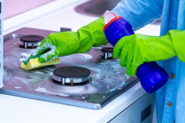 Casalinga in guanti di gomma che lava la stufa a gas con spugna e prodotti per la pulizia