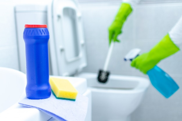 Casalinga in guanti di gomma che pulisce e disinfetta la toilette usando prodotti per la pulizia e una spazzola. servizio di pulizia