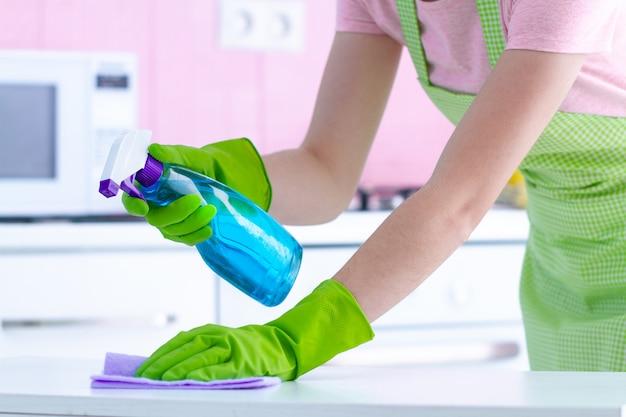 Casalinga in guanti di gomma protettivi che pulisce la polvere dal tavolo in cucina a casa con uno straccio e uno spray.