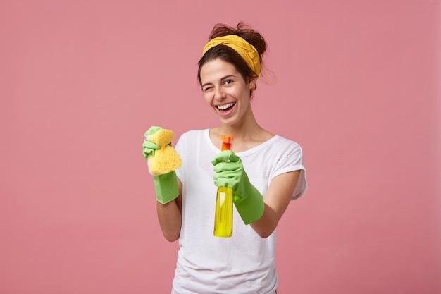 Casalinga in maglietta bianca e guanti verdi che tengono spugna e detergente nelle mani lampeggianti con gli occhi che hanno un'espressione felice durante il lavaggio. giovane femmina graziosa che fa il lavoro domestico