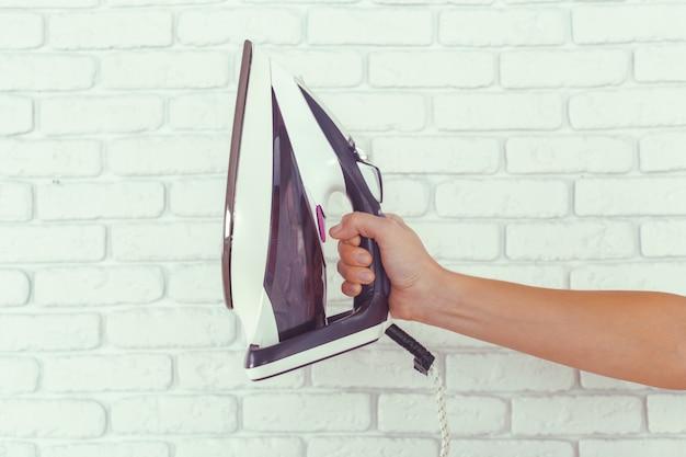 Casalinga portando un enorme mucchio di bucato sull'asse da stiro