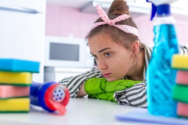Casalinga stanca, oberata di lavoro, triste in guanti di gomma protettivi che riposa dalla pulizia della casa.