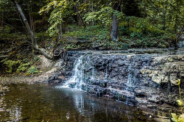 Cascata che cade da una cascata di roccia. cascata nell'estate sul piccolo fiume in lettonia, stati baltici.