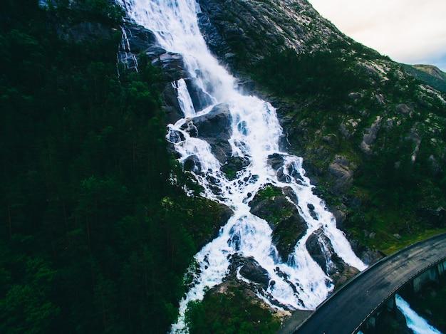 Cascata di langfoss di montagna estate sul pendio (etne, norvegia). foto aerea droni