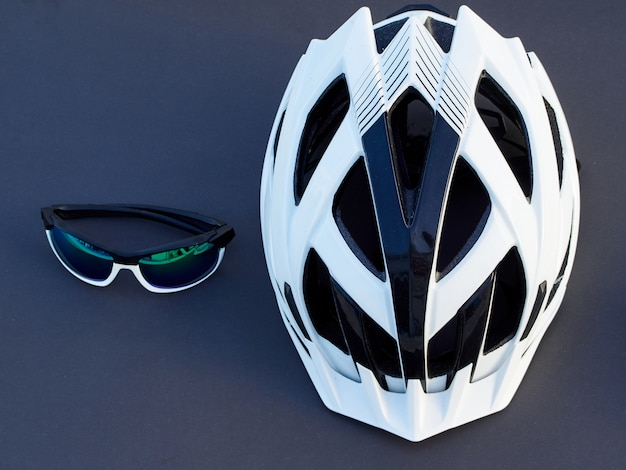 Casco da bicicletta bianco e occhiali da sole sportivi