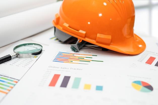 Casco da costruzione giallo con blueprint sul grafico, concetto di sicurezza ingegnere.