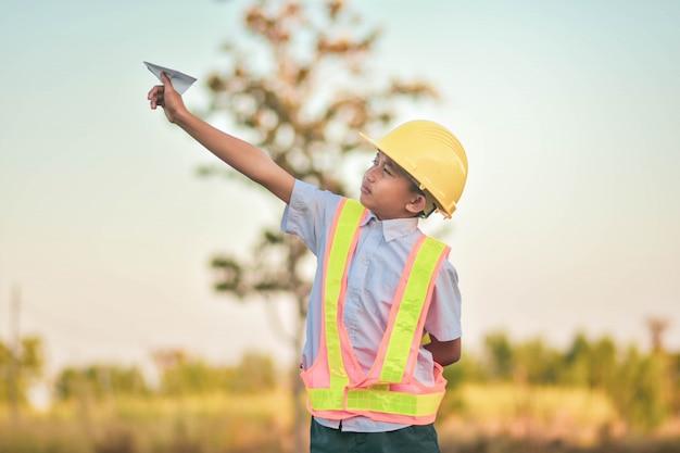 Casco dell'ingegnere del bambino del ragazzo che tiene aereo dell'aereo sogno per pilotare concetto futuro di ingegneria