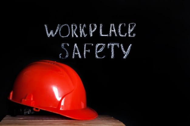 Casco di costruzione su uno sfondo nero con la sicurezza sul posto di lavoro dell'iscrizione