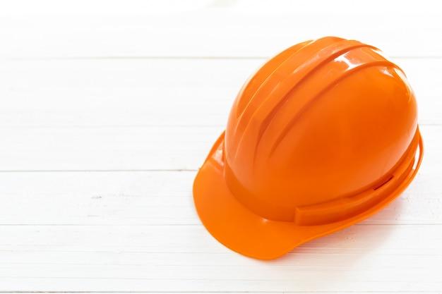 Casco di sicurezza caporeparto o dell'ingegnere su fondo di legno bianco.