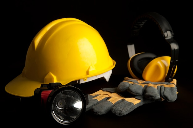 Casco di sicurezza giallo, guanto di pelle, lampada frontale, cuffia su sfondo nero.