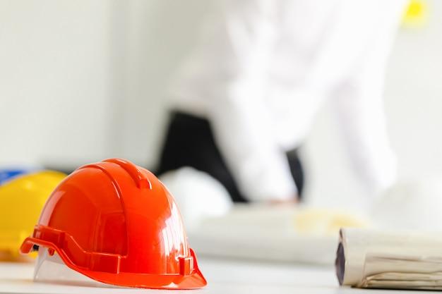 Casco di sicurezza sul tavolo in ufficio, concetto di ingegnere lavoro di squadra di costruzione di edifici
