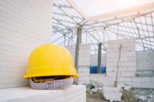 Casco giallo sopra al cantiere, concetti di costruzione del casco e del guanto.