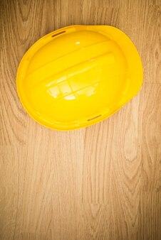 Casco protettivo industriale giallo su di legno