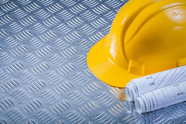 Casco rotolato dei disegni di ingegneria sul concetto scanalato della costruzione del fondo del metallo