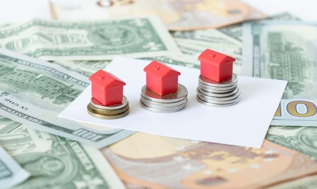 Case in miniatura che poggiano sul concetto di pile di monete da una sterlina per la scala di proprietà, mutui e investimenti immobiliari