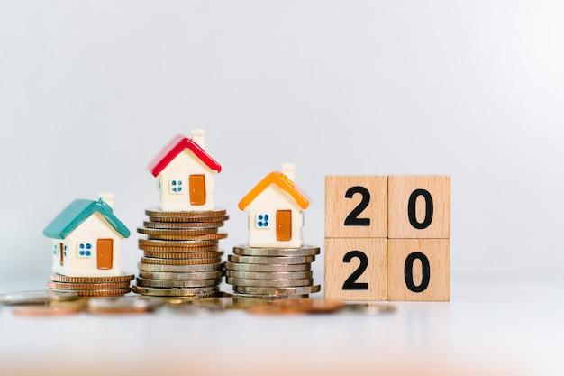 Case in miniatura sulla pila di monete con l'anno 2020 in blocchi di legno